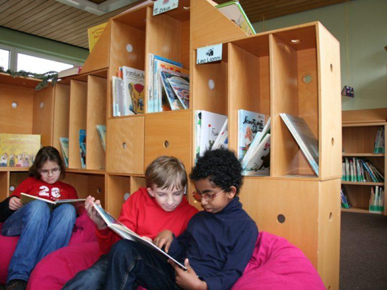 drei Kinder lesen in der Bücherei der Grundstufe