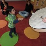 Kleines Kind trommelt auf einer Trommel.