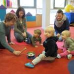 Kleinkinder mit ihren Müttern lauschen einer Klangschale.