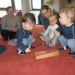Kinder, die ein Hörgerät tragen, spielen auf einem Metallophon.