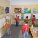 Kinder malen auf Leinwände, die an einer Wand angebracht sind.