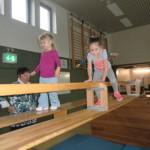 In der Sporthalle klettern Kinder über eine Bank.