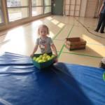 In der Sporthallte sammelt ein Kind Tennisbälle auf.