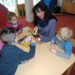 Vier Kinder und eine Erzieherin an einem Tisch unterhalten sich über eine Spielfigur aus einem Gesellschaftsspiel.