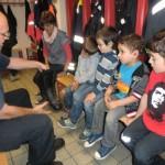 Bei einem Besuch bei der Feuerwehr bekommen vier Kinder die Ausrüstung erklärt.