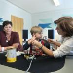 Frau Tiede erklärt einem Jungen die Hörmessung.