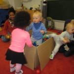 Drei Kleinkinder spielen mit einer Kiste, die mit Plastikbällen gefüllt ist.