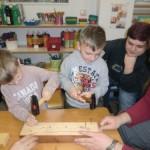 Zwei Kinder schlagen mit einem Hammer Nägel in ein Holzbrett.