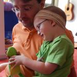 Ein Junge und sein Vater spielen gemeinsam mit einer Puppe.