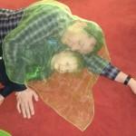Ein Junge und sein Vater liegen unter einem durchsichtigen Tuch.