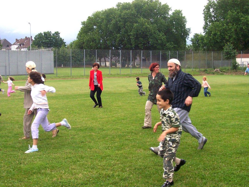 Eltern rennen mit ihren Kindern über eine Wiese