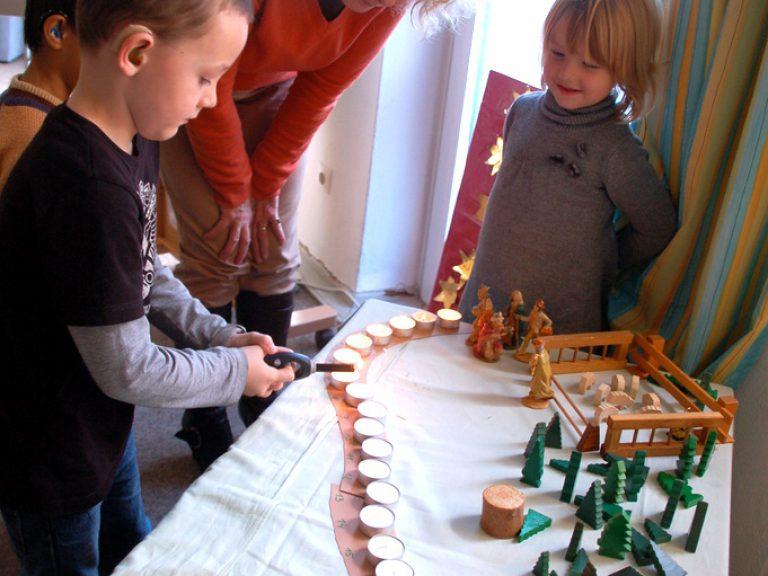 Kinder zünden eine lange Reihe Kerzen an, die die verbleibenden Tage bis Heiligabend verdeutlichen.