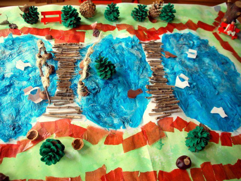 Aus Transparentpapier, bemalten Tannenzapfen und Pappmaché gebastelte Teichlandschaft.
