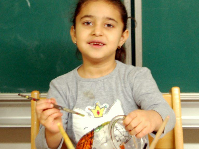 Ein Mädchen mal mit Glasfarben auf einem Einmachglas.