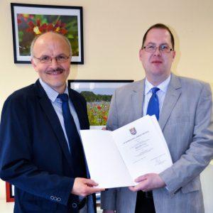 Herr Dr. Erik Dinges überreicht Herrn Drach die Ernennungsurkunde