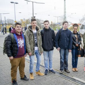 Das ist ein Gruppenbild der Klasse AH3 am Bahnhof Friedrichsdorf. Im Hintergrund sieht man einen Zug der Hessischen Landesbahn.