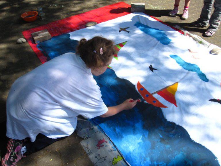 Eine Schülerin bemalt ein Betttuch für die Theaterkulisse