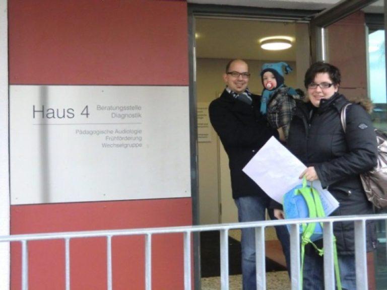 """Eltern mit Kleinkind auf dem Arm vor dem Eingang des """"Haus 4"""", in dem sich die Wechselgruppe befindet"""