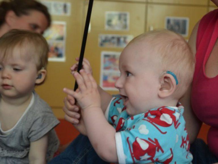 Mutter hält Baby, das ein Hörgerät trägt, auf dem Arm und sie schwingen gemeinsam den Schlegel zum Instrumentenspiel.