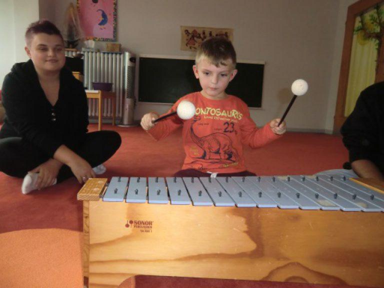 Kind spielt auf einem Metallophon.