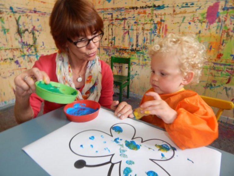 Kind malt mit einer Erzieherin einen Schmetterling.