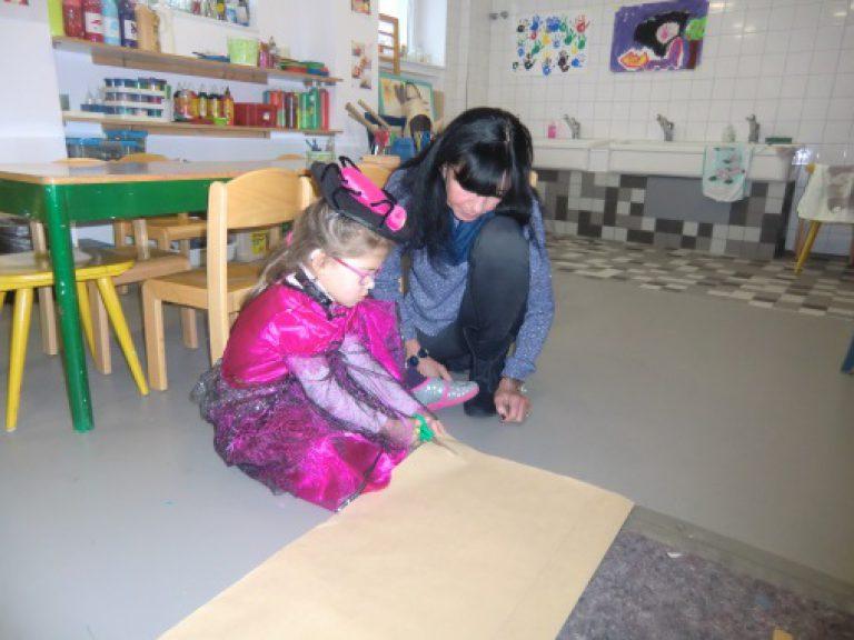 Verkleidetes Mädchen schneidet eine großes Papier.