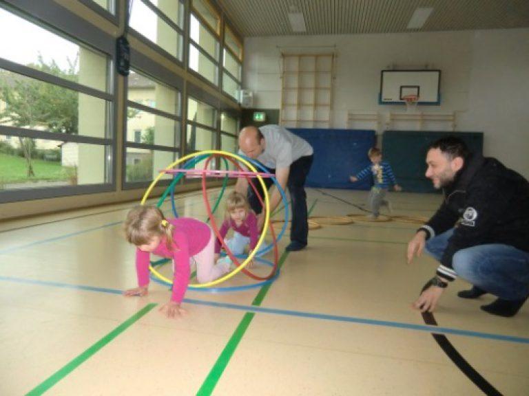 In der Sporthalle klettern Kinder durch einen Parcour, der aus Reifen aufgebaut ist.