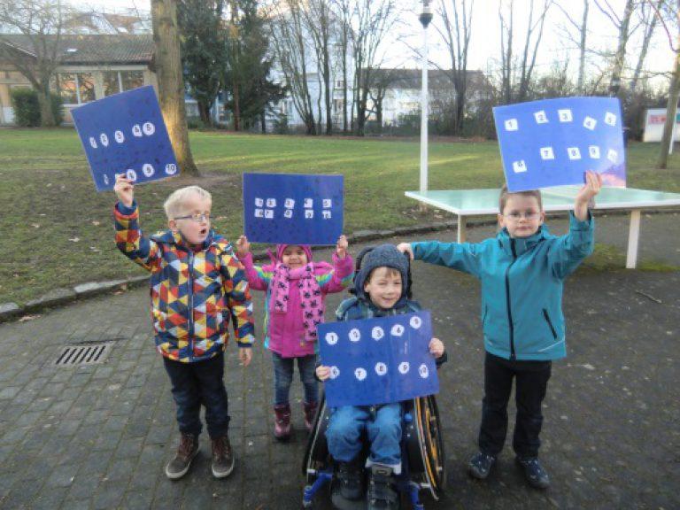 Vier Kinder zeigen auf dem Schulhof selbstgebastelte Plakate mit den Ziffern 1 bis 10.
