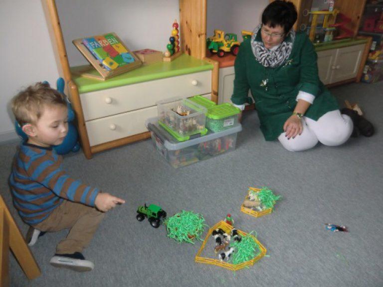 Ein Kind hat aus Spielfiguren einen Bauernhof gebaut und zeigt und beschreibt ihn einer Erzieherin.
