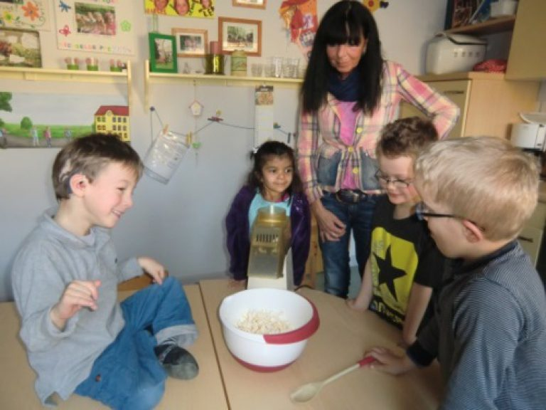 Vier Kinder stellen mit einer Erzieherin zusammen Popcorn her.