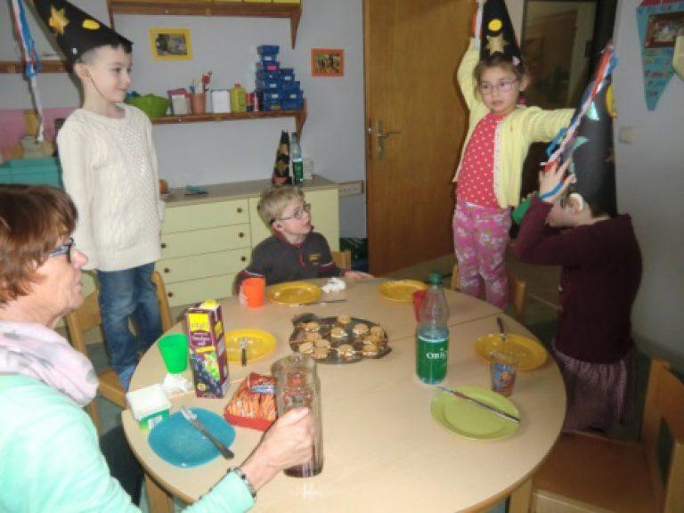 Vier Kinder mit Zauberhüten auf dem Kopf haben einen Tisch für das gemeinsame Essen gedeckt.