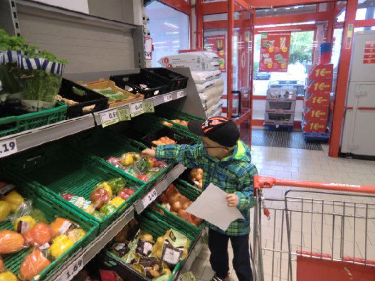 Ein Junge nimmt im Supermarkt Gemüse aus dem Gemüseregal.