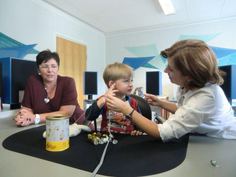 Frau Tiede bereitet gemeinsam mit einem Jungen die Hörmessung mit Einsteckhörern vor.