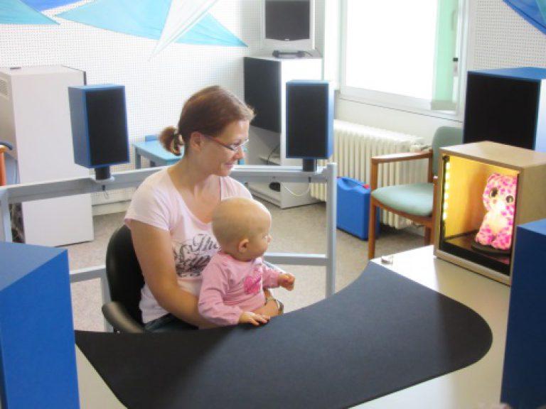 Eine Mutter hält ihr Baby auf dem Schoß und es wird eine Hörmessung mit der Looky-Box durchgeführt.