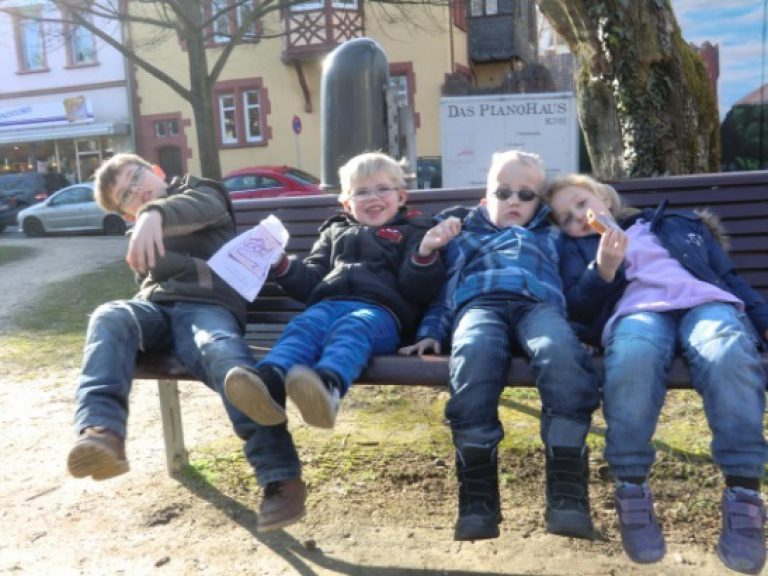 Vier Kinder sitzen im Freien auf einer Bank.