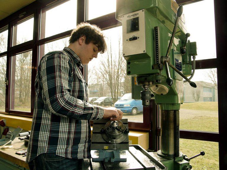 Ein Schüler bearbeitet an der Ständerbohrmaschine ein Werkstück.