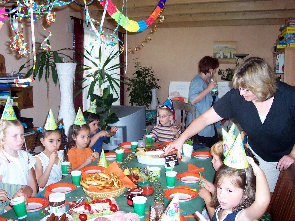 Kinder sitzen an einem Tisch, der mit Luftschlangen und Girlanden geschmückt ist. Sie feiern einen Geburtstag.