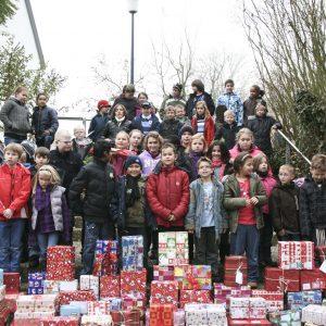 Viele Kinder der Grundstufe und ihre Weihnachtspäckchen