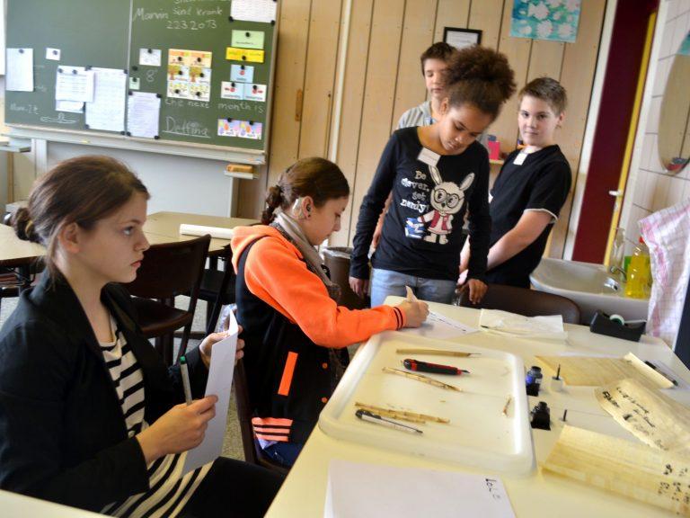 Delfina hilft beim Schreiben mit Federkiel und Schreibrohr.