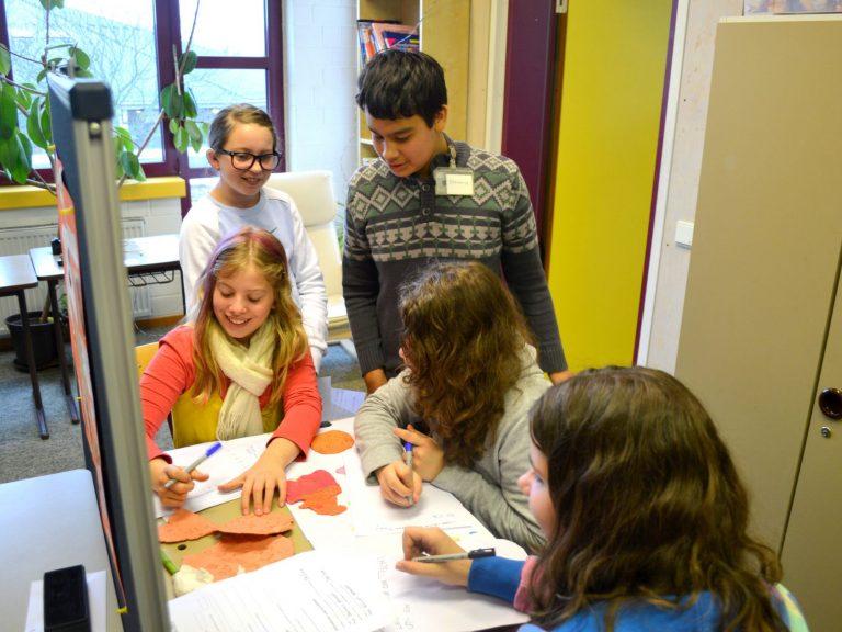 Die Besucher schreiben einen Brief in Keilschrift.