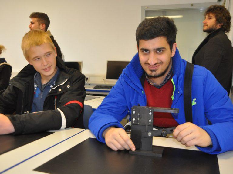 Ahmet und Alexander begutachten ein Werkstück der 'AZUBIS Indutriemechaniker