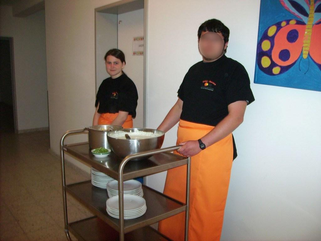 Zwei Mitarbeiteiter der Schülerfirma warten auf die hungrigen Gäste