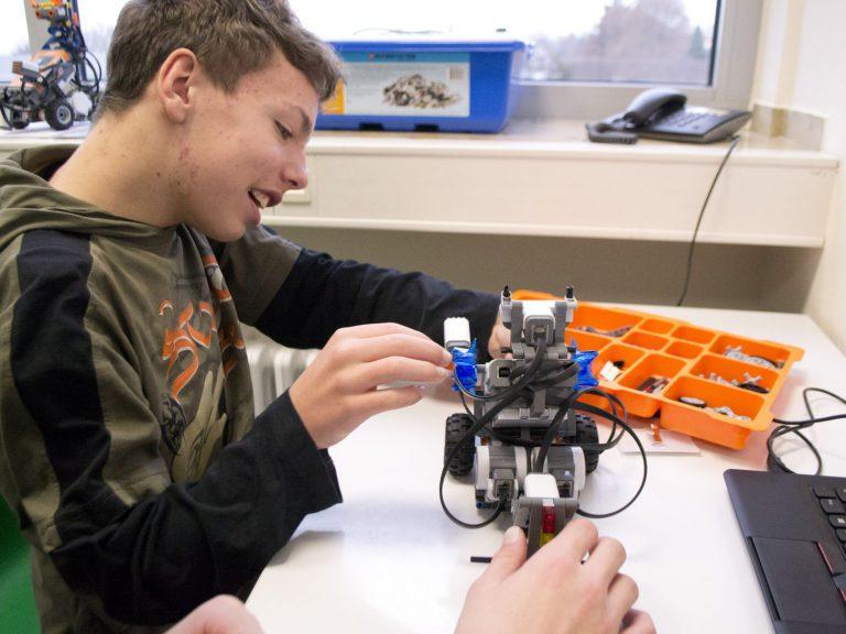 Julian baut einen Geräuschsensor an den Roboter.