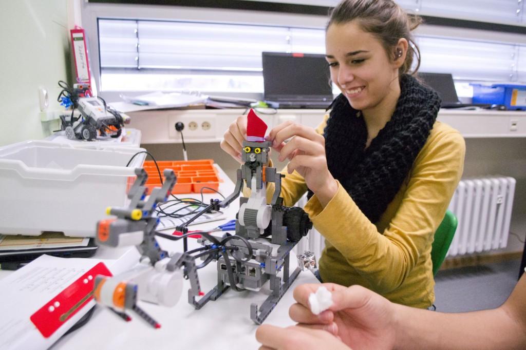 Alessandra schmückt einen Roboter als Weihnachtsmann.