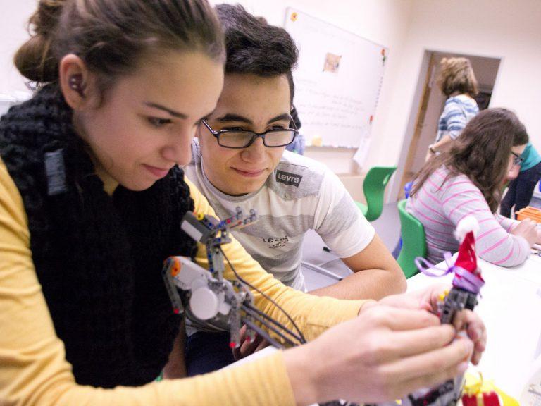 Alessandra und Metin verkleiden einen Roboter als Weihnachtsmann.