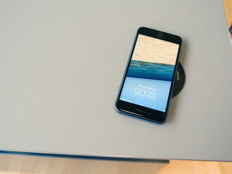 Derselbe Schreibtisch zeigt eine induktive Ladestelle, um das Handy aufzuladen
