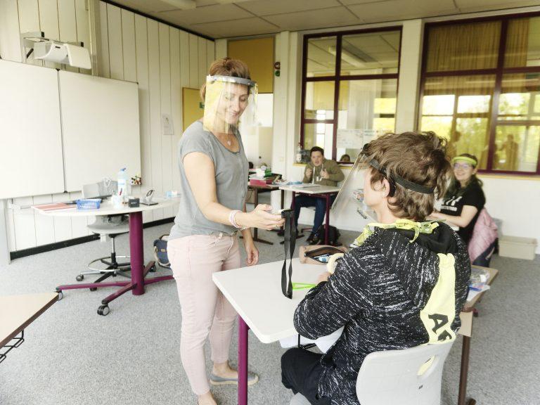 Frau Careddu koppelt einen Schüler mit der Höranlage. Zur Sicherheit tragen die Lehrerin und Schüler ein Face Shield.