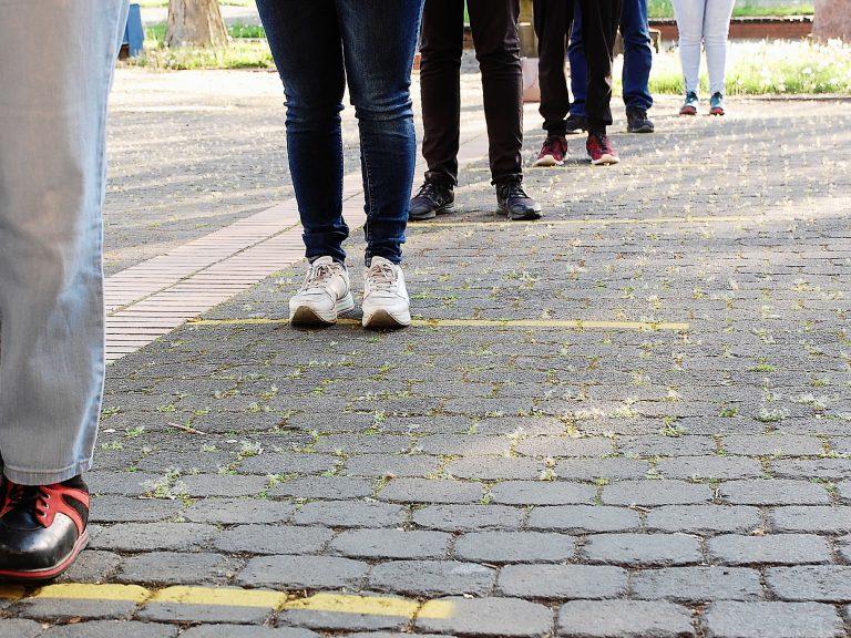 Die Schülerinnen und Schüler üben auf dem Pausenhof das Einhalten des richtigen Abstandes.