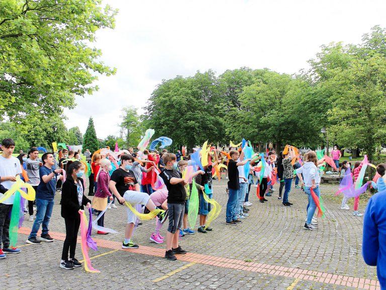 Alle Kinder tanzen mit bunten Tüchern einen Tanz.